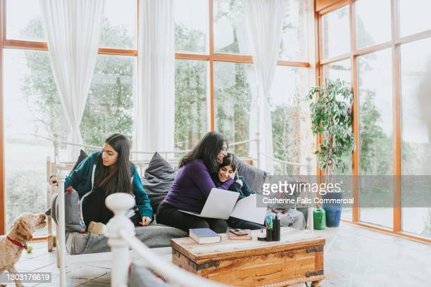 daughters homeschool on either side of their working mum - working stock pictures, royalty-free photos & images