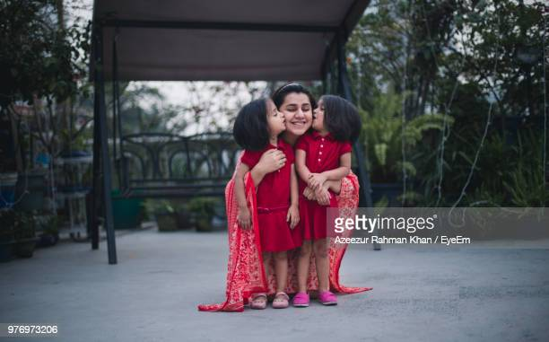 Daughters Kissing Mother In Park