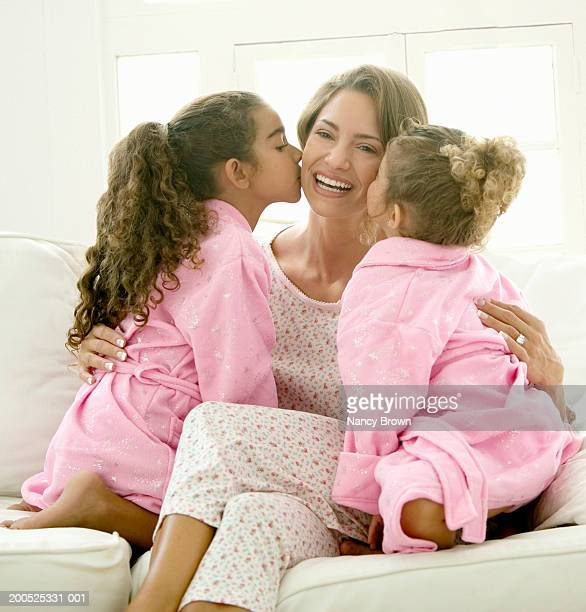 daughters (4-6) kissing mother, wearing nightwear, smiling - good night kiss stock pictures, royalty-free photos & images