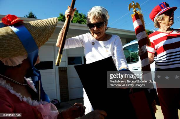 Daughters of the Revolution Ann Holst Mary Anne Eckert and Sloan Schwindt put together American flags during the Louisville Labor Day Parade in...
