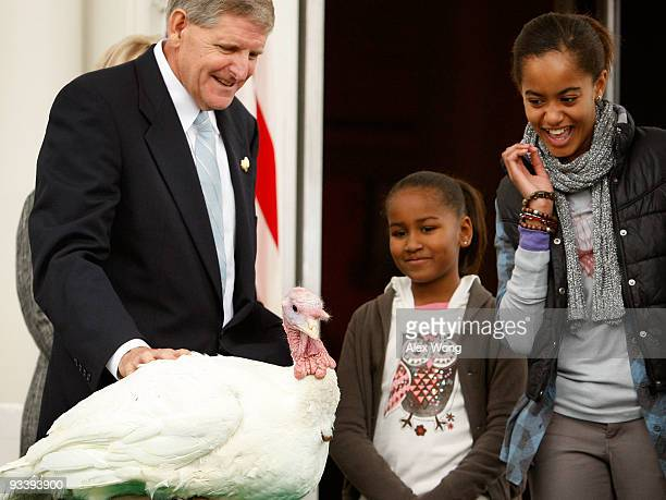 Daughters of US President Barack Obama Malia and Sasha look at a turkey named Courage with Walter Pelletier Chairman of the National Turkey...