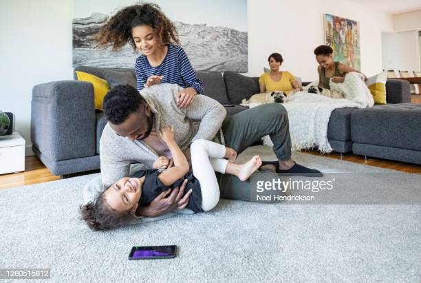 daughters pile on their dad in the family living room - girl wrestling stock pictures, royalty-free photos & images