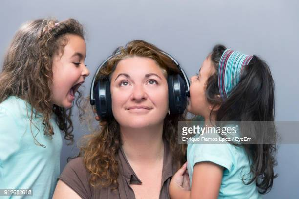 Daughters Shouting Amidst Mother Wearing Headphones By Wall