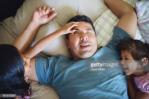 daughter's waking up their father - waking up stock pictures, royalty-free photos & images