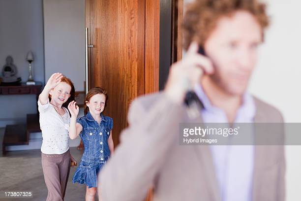 Daughters waving goodbye to father