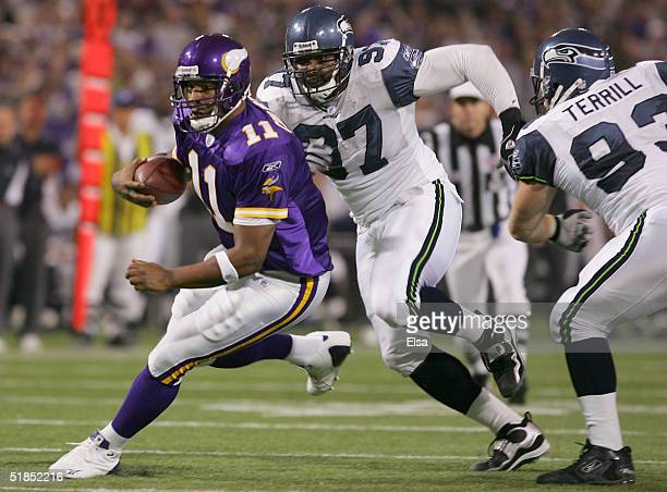 Daunte Culpepper of the Minnesota Vikings scrambles as Brandon Mitchell of the Seattle Seahawks is on his heals on December 12 2004 at the Hubert H...