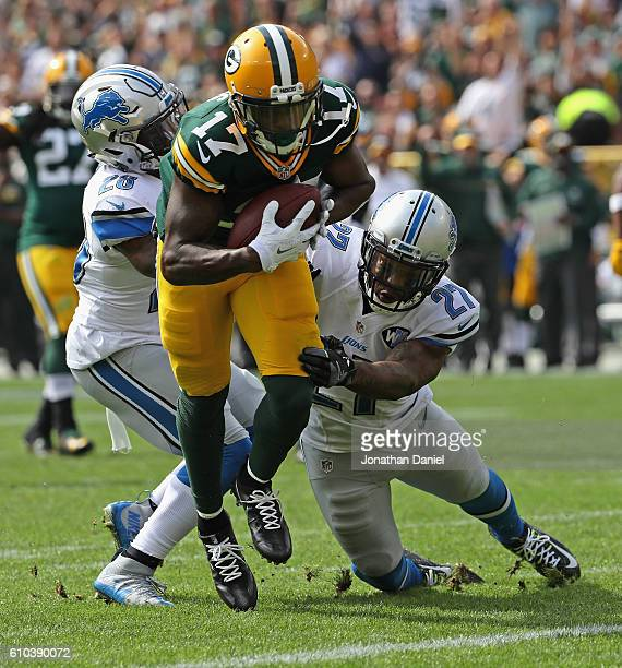 Davante Adams of the Green Bay Packers breaks a tackle attempt by Glover Quin and Quandre Diggs of the Detroit Lions to score a first quarter...