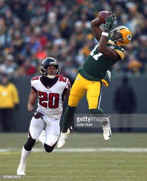 Davante Adams of the Green Bay Packers catches a pass in front of Isaiah Oliver of the Atlanta Falcons during the first half of a game at Lambeau...