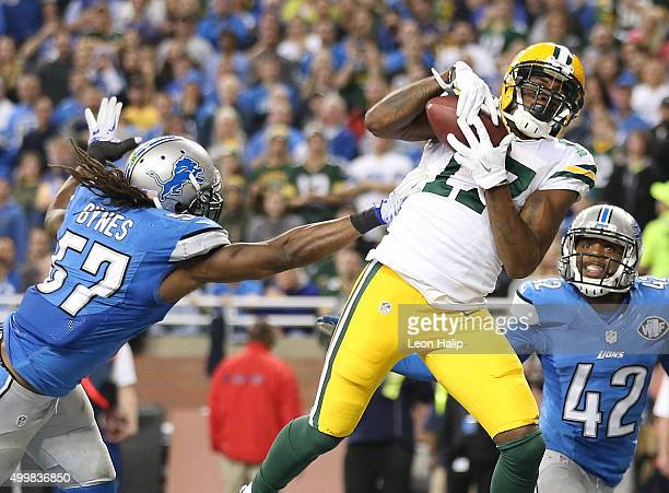 Davante Adams of the Green Bay Packers catches a third quarter touchdown pass in front of Josh Bynes of the Detroit Lions on December 3 2015 at Ford...