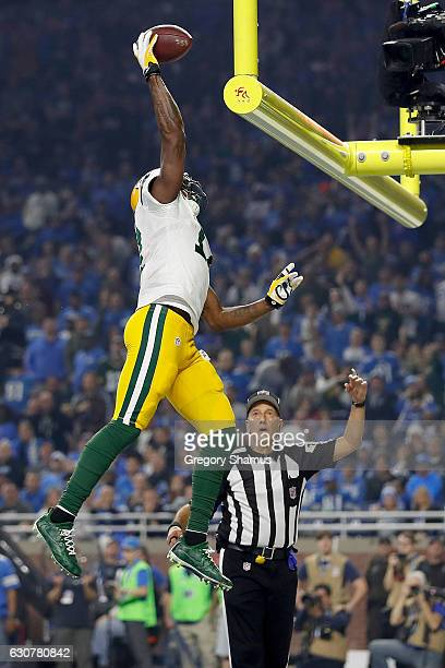 Davante Adams of the Green Bay Packers gets ready to spike the ball over the goal post after scoring a touchdown during third quarter action against...