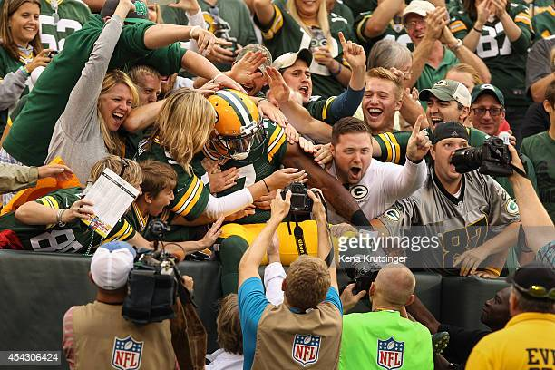 Davante Adams of the Green Bay Packers jumps into the crowd after scoring in the first quarter in the preseason game against the Kansas City Chiefs...