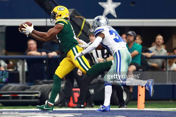 Davante Adams of the Green Bay Packers reaches for a touchdown pass ahead of Anthony Brown of the Dallas Cowboys in the first quarter of a football...