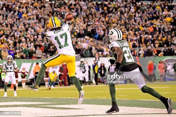Davante Adams of the Green Bay Packers scores the game winning touchdown reception past Morris Claiborne of the New York Jets during overtime at...