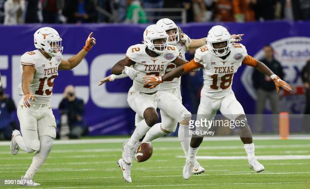 Davante Davis of the Texas Longhorns celebrates with this teammates after an interception late in the fourth quarter against the Missouri Tigers at...
