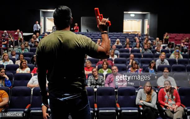 Dave Acosta founder of Fight Back holds a dummy handgun as he talks about how to react and fight back during an active shooter event to teachers from...