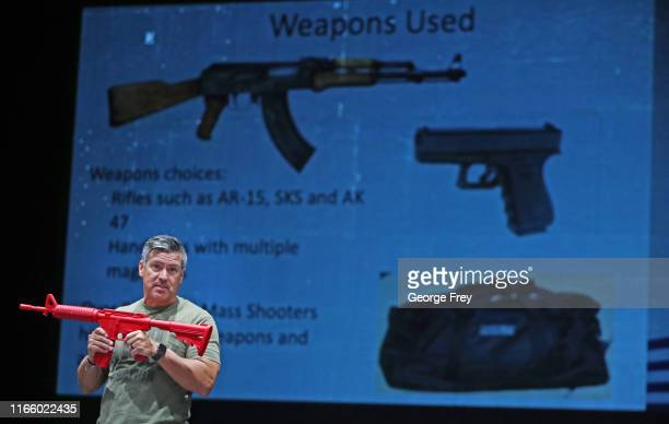 Dave Acosta founder of Fight Back holds a dummy rifle as he talks about how to react and fight back during an active shooter event to teachers from...