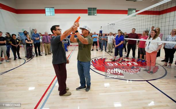 Dave Acosta founder of Fight Back uses a dummy handgun as he demonstrates with a teacher how to disarm a shooter and fight back during an active...