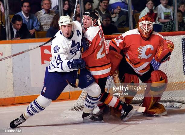 Dave Andreychuk of the Toronto Maple Leafs skates against Trevor Kidd and Sheldon Kennedy of the Calgary Flames during NHL game action on March 4...