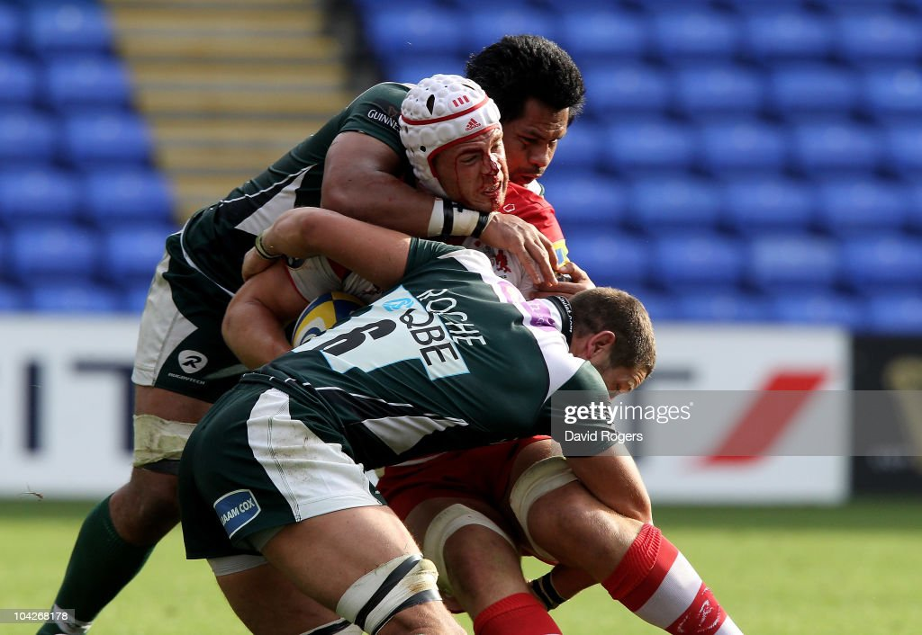 Dave Attwood of Gloucester is tackled by George Stowers and Kieran Roche during the Aviva Premiership match between London Irish and Gloucester at the Madejski Stadium on September 19, 2010 in Reading, England.