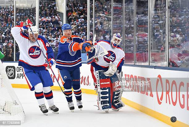 Dave Babych and Bob Essensa of the Winnipeg Jets alumni battle for the puck with Craig Simpson of the Edmonton Oilers alumni during the 2016 Tim...