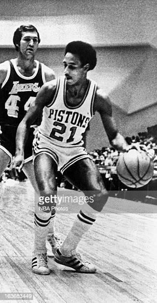 Dave Bing of the Detroit Pistons dribbles the ball against Jerry West of the Los Angeles Lakers during a game played circa 1970 at Cobo Arena in...