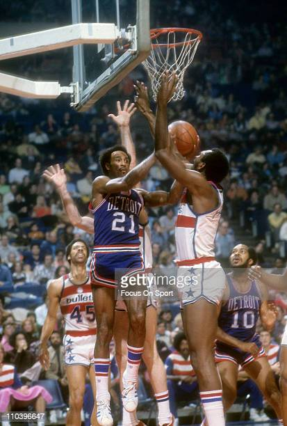 Dave Bing of the Detroit Pistons goes up to shoot against Elvin Hayes of the Washington Bullets during an NBA basketball game circa 1974 at the...