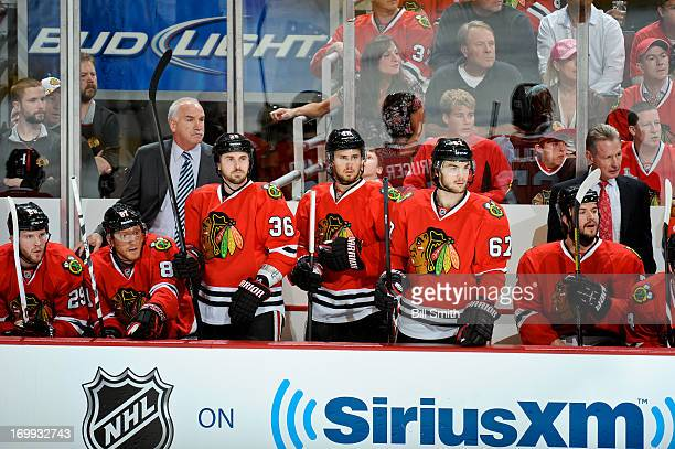 Dave Bolland Marcus Kruger and Michael Frolik of the Chicago Blackhawks stand in the bench in front of head coach Joel Quenneville in Game One of the...