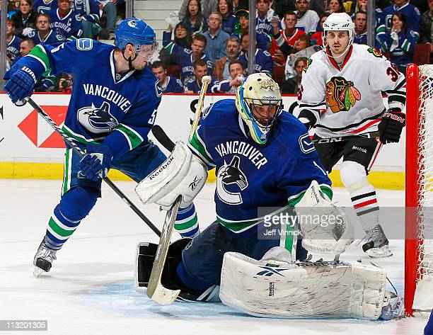 Dave Bolland of the Chicago Blackhawks and Christian Ehrhoff of the Vancouver Canucks look on as Roberto Luongo of the Vancouver Canucks makes a save...