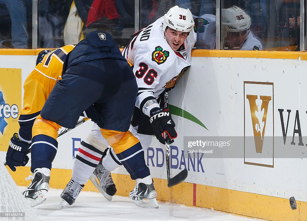 Dave Bolland #36 of the Chicago Blackhawks battles along the boards against Sergei Kostitsyn #74 of the Nashville Predators during an NHL game at the Bridgestone Arena on February 10, 2013 in Nashville, Tennessee.