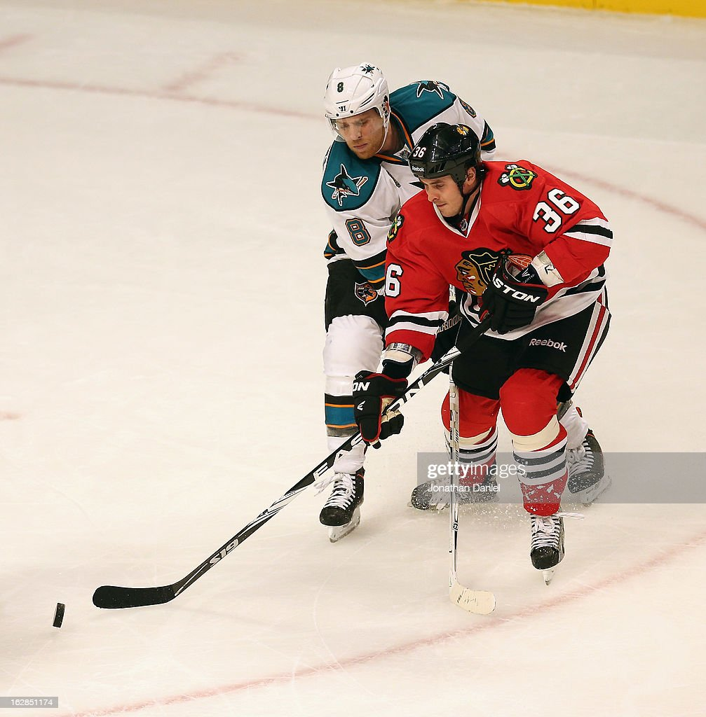 Dave Bolland #36 of the Chicago Blackhawks controls the puck under pressure from Joe Pavelski #8 of the San Jose Sharks at the United Center on February 15, 2013 in Chicago, Illinois. The Blackhawks defeated the Sharks 4-1.