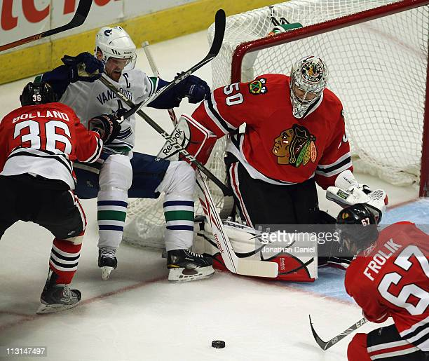 Dave Bolland of the Chicago Blackhawks knocks down Henrik Sedin of the Vancouver Canucks as Corey Crawford rejects a shot and Micahel Frolik moves in...