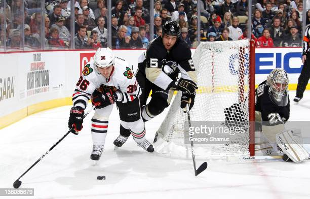 Dave Bolland of the Chicago Blackhawks moves the puck in front of Deryk Engelland and Marc-Andre Fleury of the Pittsburgh Penguins on December 20,...