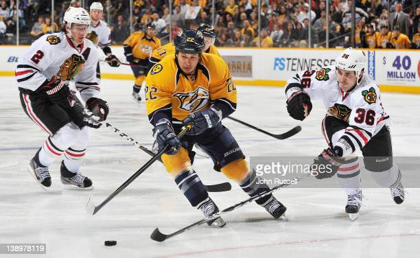 Dave Bolland of the Chicago Blackhawks pokes the puck from Jordin Tootoo of the Nashville Predators during an NHL game at the Bridgestone Arena on...