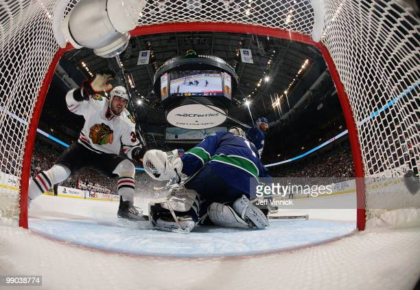 Dave Bolland of the Chicago Blackhawks scores on goalie Roberto Luongo of the Vancouver Canucks as Pavol Demitra of the Canucks skates by in Game 6...