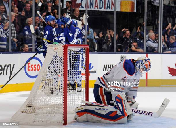 Dave Bolland of the Toronto Maple Leafs celebrates his overtime goal with teammates as Devan Dubnyk of the Edmonton Oilers looks on during NHL game...