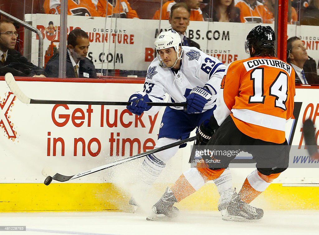 Dave Bolland #63 of the Toronto Maple Leafs passes the puck as Sean Couturier #14 of the Philadelphia Flyers defends during the second period at Wells Fargo Center on March 28, 2014 in Philadelphia, Pennsylvania. The Flyers defeated the Maple Leafs 4-2.