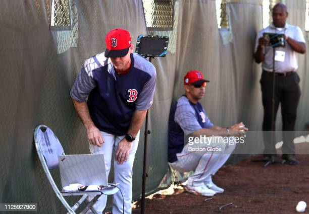 Dave Bush minor league pitching coordinator checks a laptop setup during a spring training bullpen session at JetBlue Park in Fort Myers FL on Feb 17...