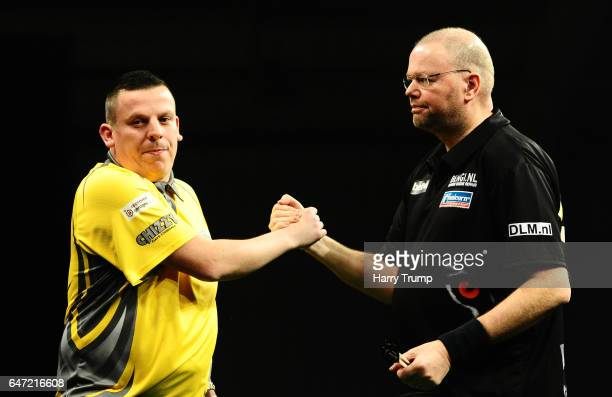 Dave Chisnall and Raymond Van Barneveld shake hands as Dave Chisnall wins during Night Five of the Betway Premier League Darts at Westpoint Arena on...