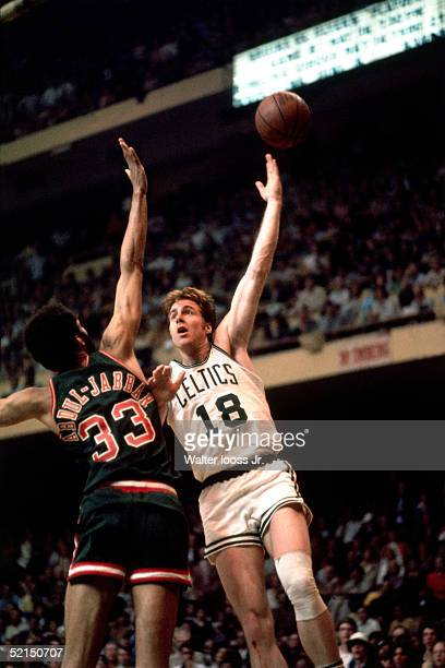 Dave Cowens of the Boston Celtics shoots a hook shot against the Kareem AbdulJabbar of the Milwaukee Bucks during an NBA game at the Boston Garden in...