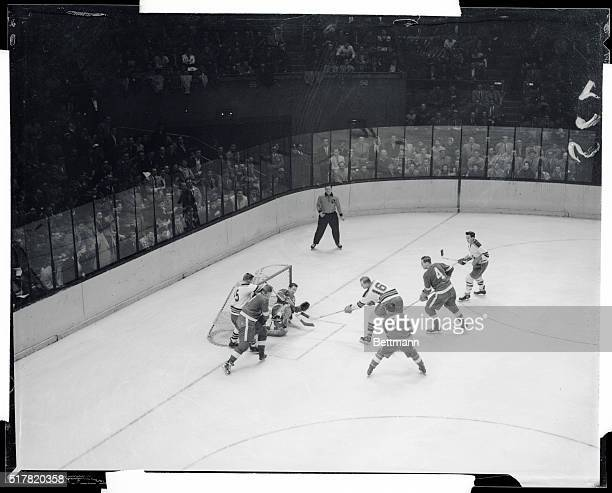 Dave Creighton of the Rangers drives the puck past Detroit Red Wings goalie Glen Hall in the first period of hockey game at the Garden Blurred object...