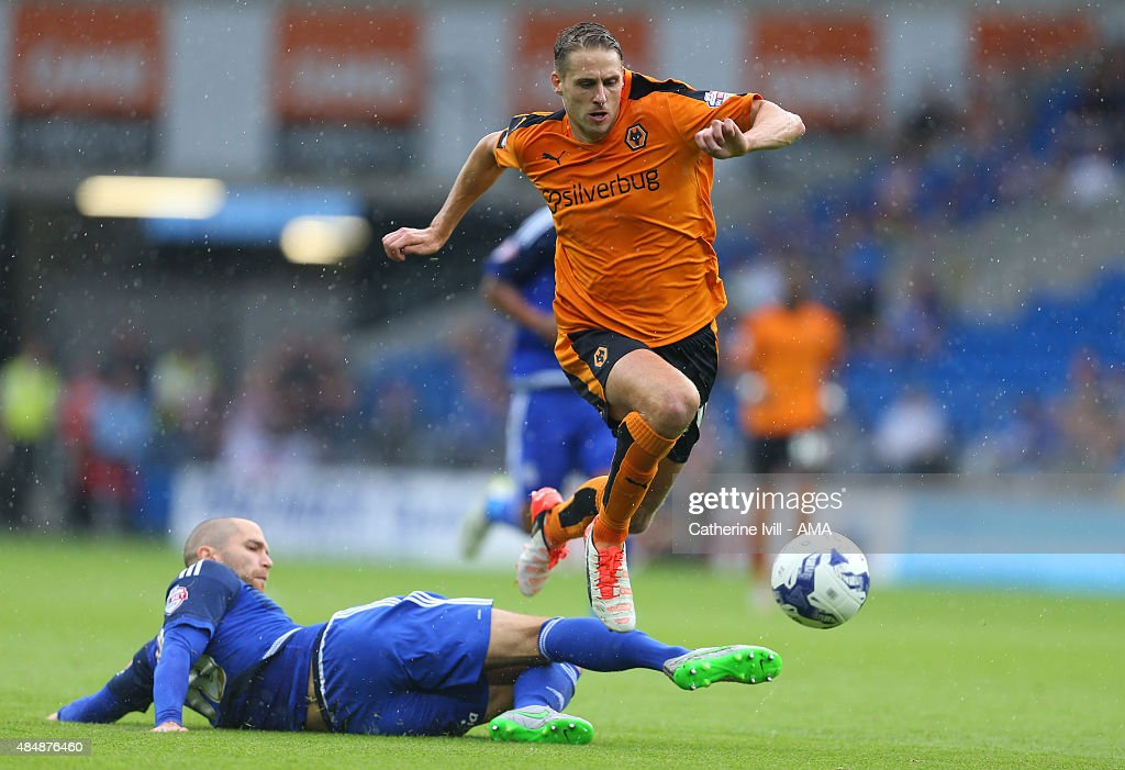 Dave Edwards of Wolverhampton Wanderers jumps over Matthew Connolly of Cardiff City during the match the Sky Bet Championship match between Cardiff City and Wolverhampton Wanderers at Cardiff City Stadium on August 22, 2015 in Cardiff, Wales.
