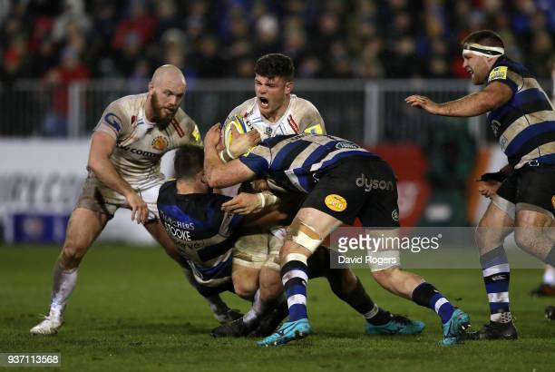 Dave Ewers of Exeter Chiefs is tackled by Elliott Stooke and Tom Ellis of Bath during the Aviva Premiership match between Bath Rugby and Exeter...