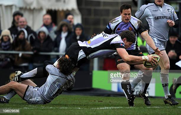 Dave Ewers of Exeter scores a try as Joe Cobden of Leicester holds on to his legs during the LV Anglo Welsh Cup match between Exeter Chiefs and...
