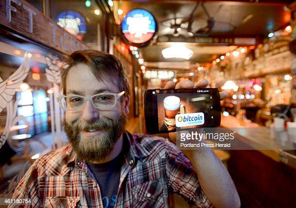 Dave Foster is media marketing manager at The Great Lost Bear in Portland displaying a Bitcoin app on his mobile phone that can be used for payment...