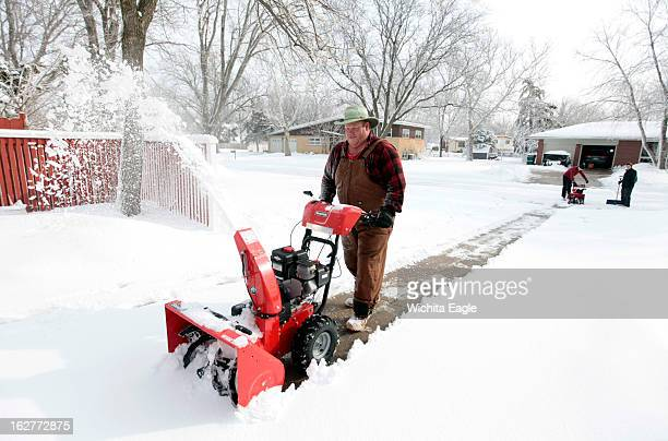Dave Franklin of Franklin's Lawn Care removes snow in Benjamin Hills in Wichita Kansas with his two sons and wife The family had 37 customers to get...