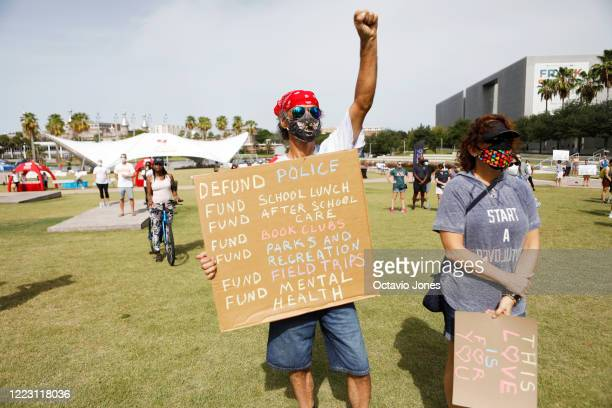 Dave Gonzalez stands in protest at the Love Walk holding a Defund Police sign before the start of the Love Walk at Curtis Hixon Park on June 27 2020...