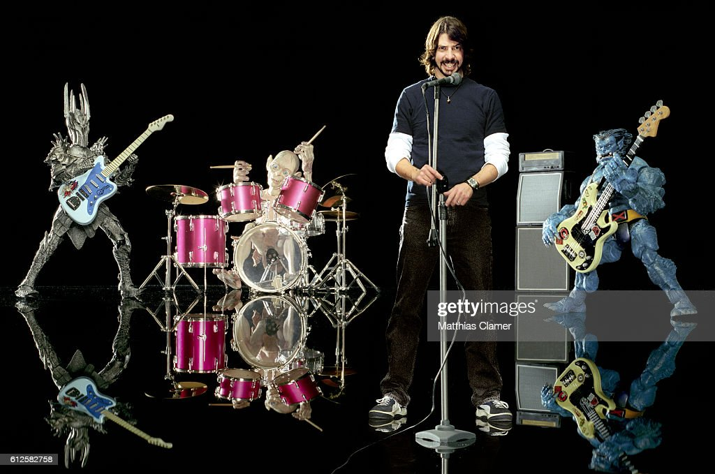 Dave Grohl sings with a band of action figures including Sauron on guitar, Gollum on drums, and The Beast from X-Men on bass guitar.