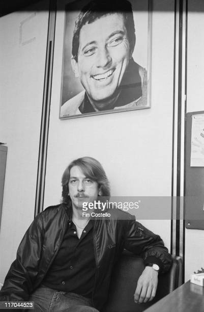Dave Holland, Britiish drummer with heavy metal band Judas Priest, poses beneath a portrait of US singer Andy Williams in Centrepoint, London,...