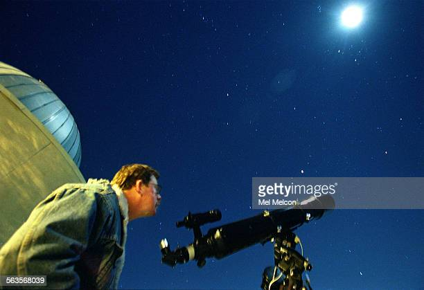 Dave Holland newsletter editor for the Ventura County Astronomical Society gazes up at the stars while standing next to his Celestron 6 inch...