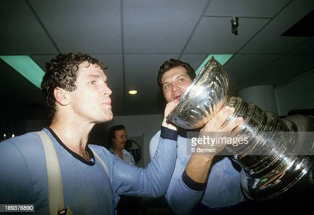 Dave Hunter and Dave Semenko of the Edmonton Oilers celebrate in the locker room with the Stanley Cup Trophy after the Oilers defeated the New York...